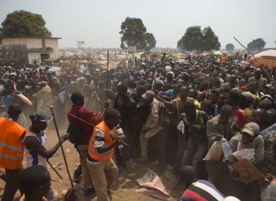 Security volunteers use sticks to fend off the crowd trying to enter a food and supplies distribution point, at a makeshift camp housing an estimated 100,000 displaced people, at Mpoko Airport, in Bangui, Central African Republic.