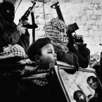 Young members of Fatah, a major Palestinian political party, at the funeral procession of a Palestinian fighter in 2002.<span class=