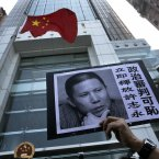 A placard with a photo of legal scholar Xu Zhiyong is raised by a demonstrator protesting against a Chinese court's decision to sentence him in prison outside the Chinese liaison office in Hong Kong. Xu was sentenced Sunday to four years in prison on the charge of disturbing order in public places. Xu's fledgling campaign became a target after it inspired people across the country to gather for dinner parties to discuss social issues and occasionally to unfurl banners in public places in small rallies. The placard reads: