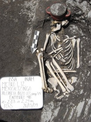 A 2009 image of the skeleton of a person lying next to an incense holder after it was found during Mexico City excavations.