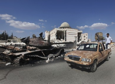 Free Syrian Army soldiers drive by a damaged Syrian military tank in Aleppo