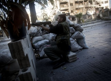 A rebel Free Syrian Army soldier shoots his machine gun towards Syrian Army positions in Aleppo