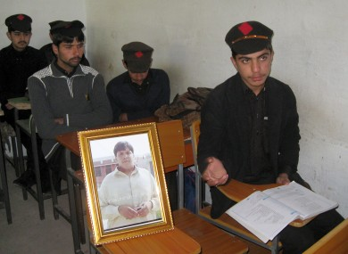 Pakistani students sit next to a picture of classmate Aitzaz Hasan, who residents and police say died this week while trying to stop a suicide bomber who was targeting his school in a remote village in Hangu.