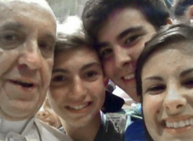 Pope Francis in a selfie from inside St Peter's Basilica with young people on pilgrimage at the Vatican.
