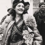 In 1942, a Russian female partisan stands covered in ammunition.<span class=
