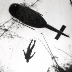 An evacuation helicopter in Vietnam raises the body of an American paratrooper killed in action in the jungle near the Cambodian border in 1966. <span class=