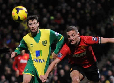 Wes Hoolahan chases the ball under the close supervision of Manchester United's Nemanja Vidic.