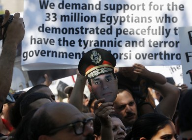 Demonstrators who support the Egyptian military hold up a mask of Egyptian Gen. Abdel Fattah al-Sisi