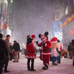 Two people dressed as Disney characters talk under falling snow in Times Square.<span class=