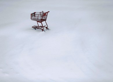 A shopping cart sits idle in a Trader Joe's parking lot during a winter snowstorm in Philadelphia.