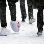 A man walks with his feet bagged during a winter snowstorm in Philadelphia<span class=