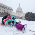 Bashon Mann and his children sled down a hill at the Capitol as snow falls in Washington.<span class=