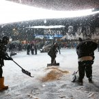 Workers shovel snow in front of Brooklyn's Barclay's Center before an NBA basketball game between the Orlando Magic and the Brooklyn Nets at the Barclays Center in New York. <span class=