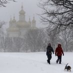 A man and woman walk a dog in a park as snow falls in Baltimore.<span class=
