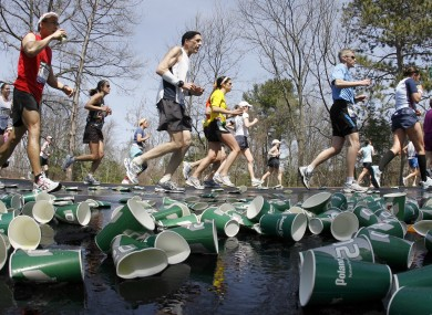 Runners make their way through discarded cups in Boston.