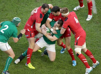 Healy gets wrapped up by three Welsh defenders.