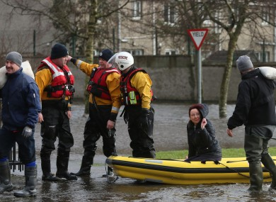 Residents use a boat to navigate flood waters after a flash flood on the Lee Estate in Limerick City last weekend.