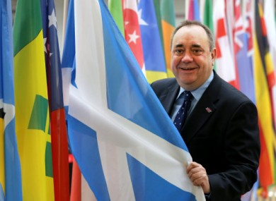 Scotland's First Minister Alex Salmond views a saltire flag at Glasgow Airport.