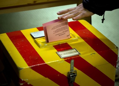 A voter puts his ballot into a box at a polling statio near Geneva today.