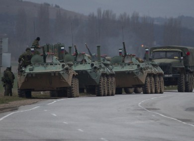 Russian armored personnel carriers and a truck are parked on the side of the road near the town of Bakhchisarai, Ukraine.