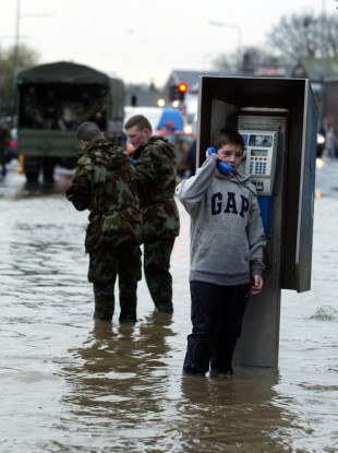 Kevin Kinsella from Ballybough speaks to a friend on a public telephone during flooding in Dublin in 2002.