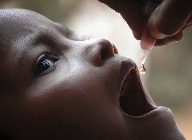 A child is given drops of polio vaccine at a health centre in India