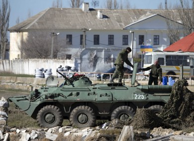 Pro-Russian soldiers in unmarked uniforms with an APC, pictured yesterday near Ukrainian marines base in the city of Feodosia, Crimea.