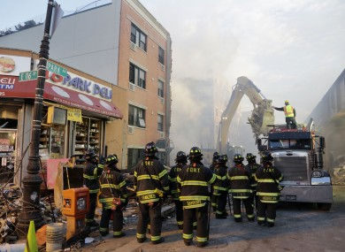Firefighters watch as a machine removes debris from the site of the explosion.