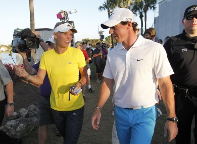 Rory McIlroy walks with his fiancee, tennis player Caroline Wozniacki, after finishing his third round at the Honda Classic