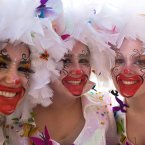A trio of revellers pose for a photo during the carnival Clowns' Parade along the waterfront in Sesimbra, south of Lisbon. Every year on Carnival Monday thousands dress as clowns to take part in the fishing village's parade. <span class=