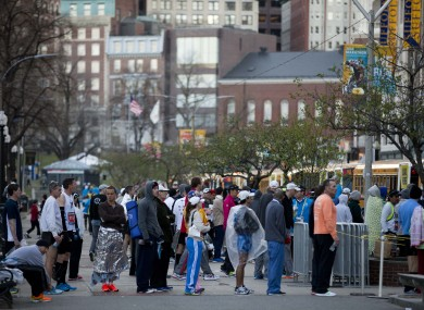 Runners queue to board busses ahead of the 118th Boston Marathon