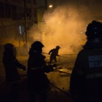 Firefighters put out a burning barricade during clashes at the Pavao Pavaozinho slum in Rio de Janeiro, Brazil. Intense exchanges of gunfire, numerous blazes set alit and a shower of homemade explosives and glass bottles onto a busy avenue in Rio de Janeiro''s main tourist zone erupted Tuesday night after the death of a popular young shantytown resident, Douglas Rafael da Silva Pereira. (AP Photo/Felipe Dana)<span class=