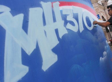 A graffiti artist works on a graffiti featuring the missing Malaysia Airlines Flight MH370 in Kuala Lumpur