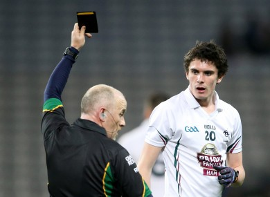 Marty Duffy shows Kildare's David Hyland a black card.