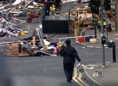 An RUC officer carries bunches of flowers down to the bomb site in Omagh
