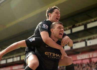 Samir Nasri helps Edin Dzeko celebrate his goal.