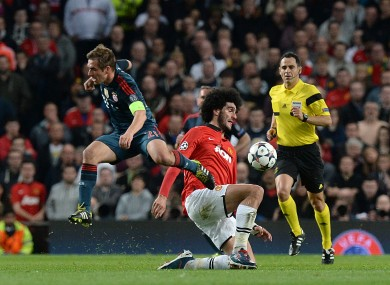 Marouane Fellaini slides in to beat Philip Lahm to the ball.