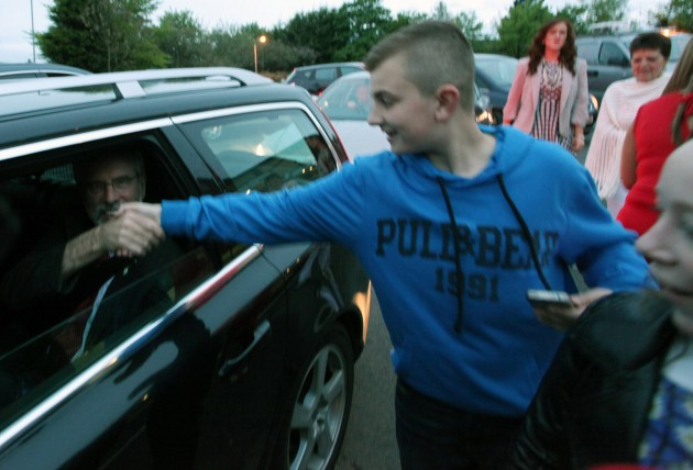 : Gerry Adams shakes hands with a young