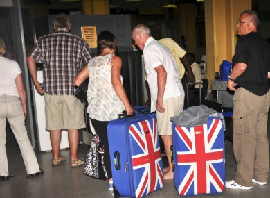 In this photo taken late Thursday, British tourists queue to prepare to leave the international airport in Mombasa.