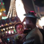 An Egyptian man holds his daughter as they celebrate Moulid outside the Sayyeda Zeinab shrine, in Cairo.<span class=