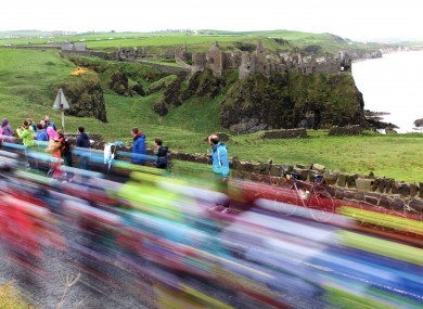 Riders pictured traveling past Dunluce Castle.