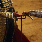 French bullfighter Sebastian Castella, left, gives his sword stained with blood to an assistant after killing with it a El Pilar ranch fighting bull during a bullfight of the San Isidro fair in Madrid. San Isidro's bullfighting fair is one of the most important fairs in the world. Bullfighting is an ancient tradition in Spain. <span class=