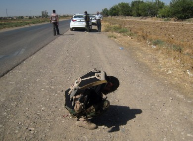 A Kurdish security officer covers his face after seeing several dead bodies in Kirkuk, Iraq.