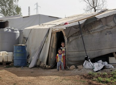 Syrian refugee children stand outside their tent at a Syrian refugee camp in the eastern Lebanese town of Majdal Anjar.