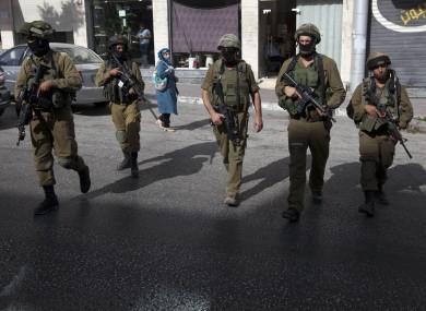Israeli soldiers walking in Hebron yesterday