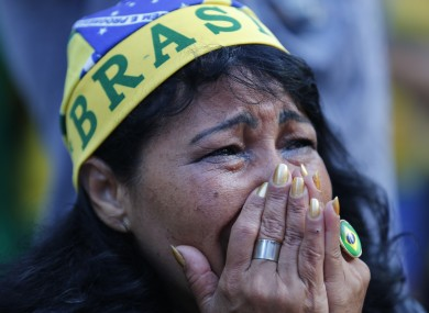 A fan of Brazil reacts as she watches as the Netherlands score a second goal against Brazil.