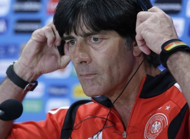 Joachim Löw adjusts a headset during a news conference.