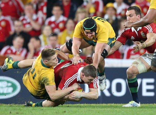 Brian O'Driscoll is tackled by James O'Connor and Liam Gill