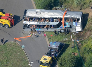 The wreckage of the bus and rescue vehicles off the motorway this morning