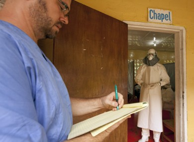 Dr Kent Brantly (left) writing prescriptions for Ebola patients in the isolation unit through the doorway before he got ill.